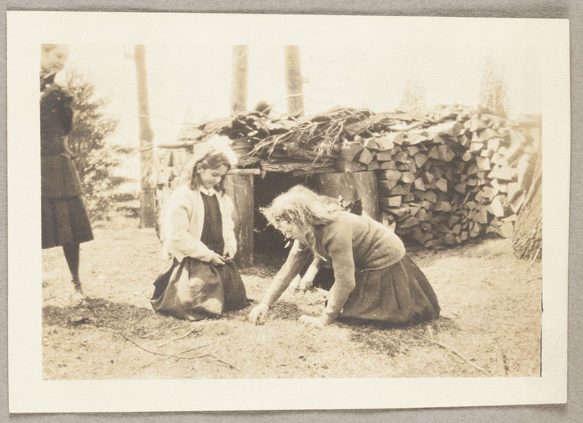 Untitled: two girls near a woodpile, presumably on the Lyman Estate in Waltham, Mass.