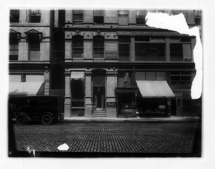 Streetscape, with store sign for 'Tailors Thomas A. Brook