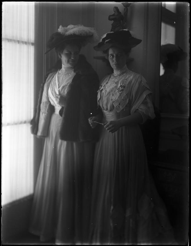 "Sisters Margaret ""Peg"" Curtis (1883-1965), left, and Harriot ""Hat"" Sumner Curtis (1881-1974), right, pose together in nice dresses and hats., Elizabeth (Tyson) Vaughan photographic collection, Vaughan, Elizabeth (Tyson), 1871-1949 (Photographer)"